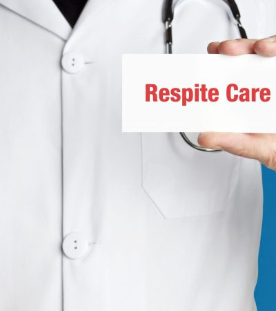 Respite Care. Doctor in smock holds up business card. The term Respite Care is in the sign. Symbol of disease, health, medicine